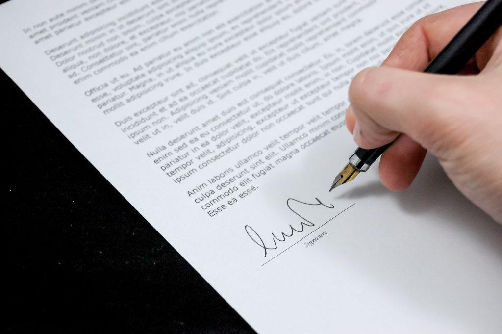 persoon zet handtekening